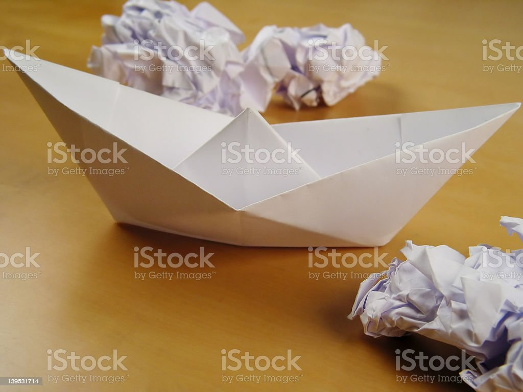 Paper boat between wads royalty-free stock photo