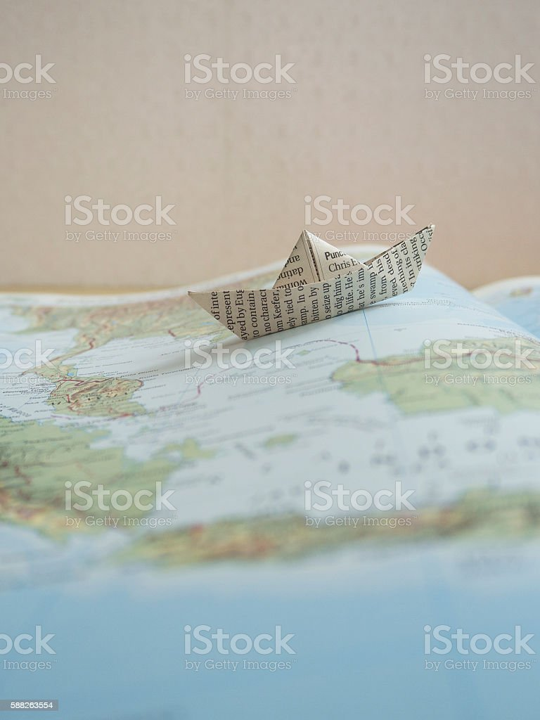 Paper Boat on map book stock photo