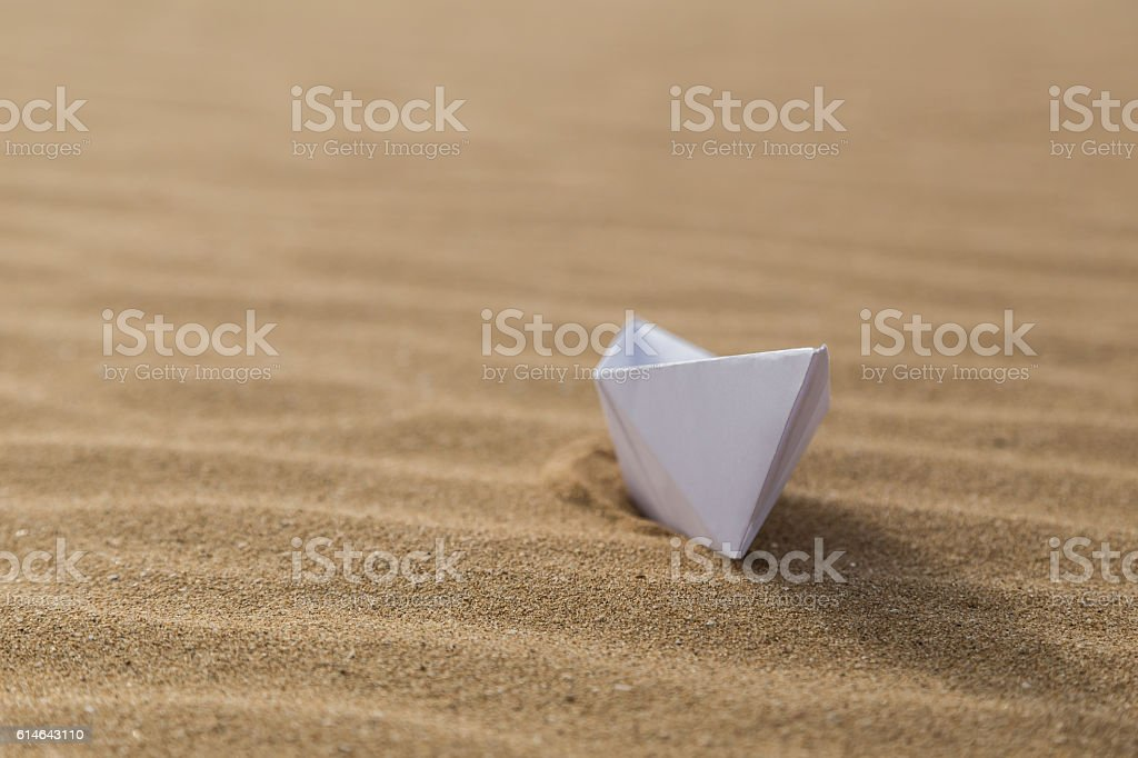 Paper boat on the sandy beach stock photo
