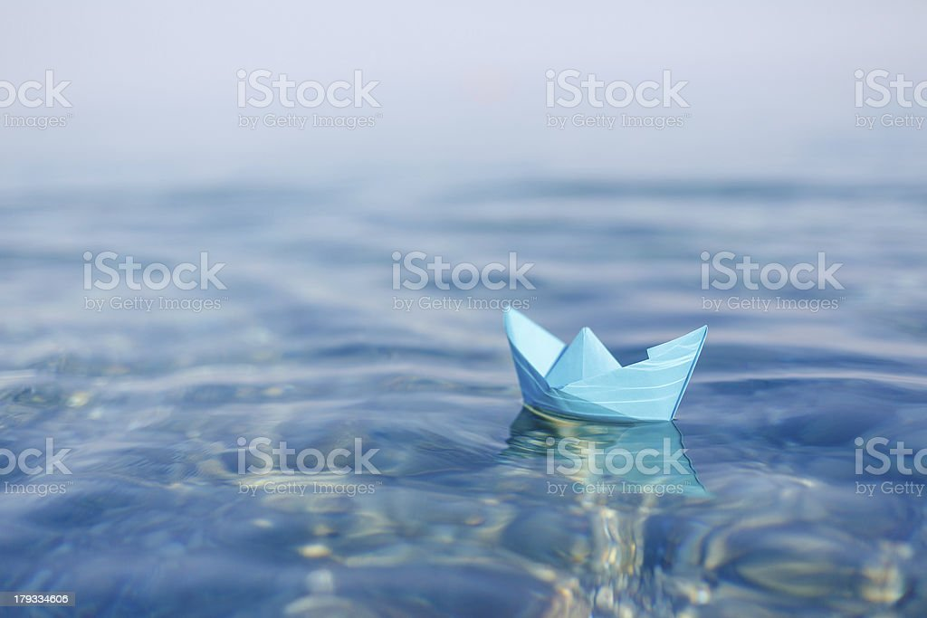 paper boat sailing on blue water surface stock photo