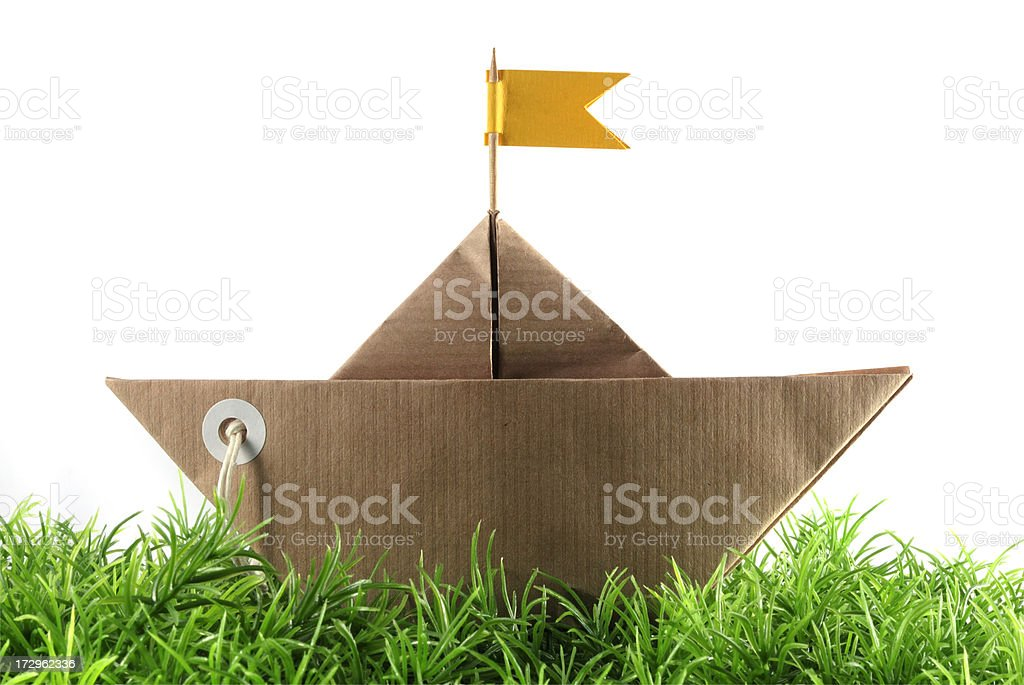 paper boat sailing on grass royalty-free stock photo