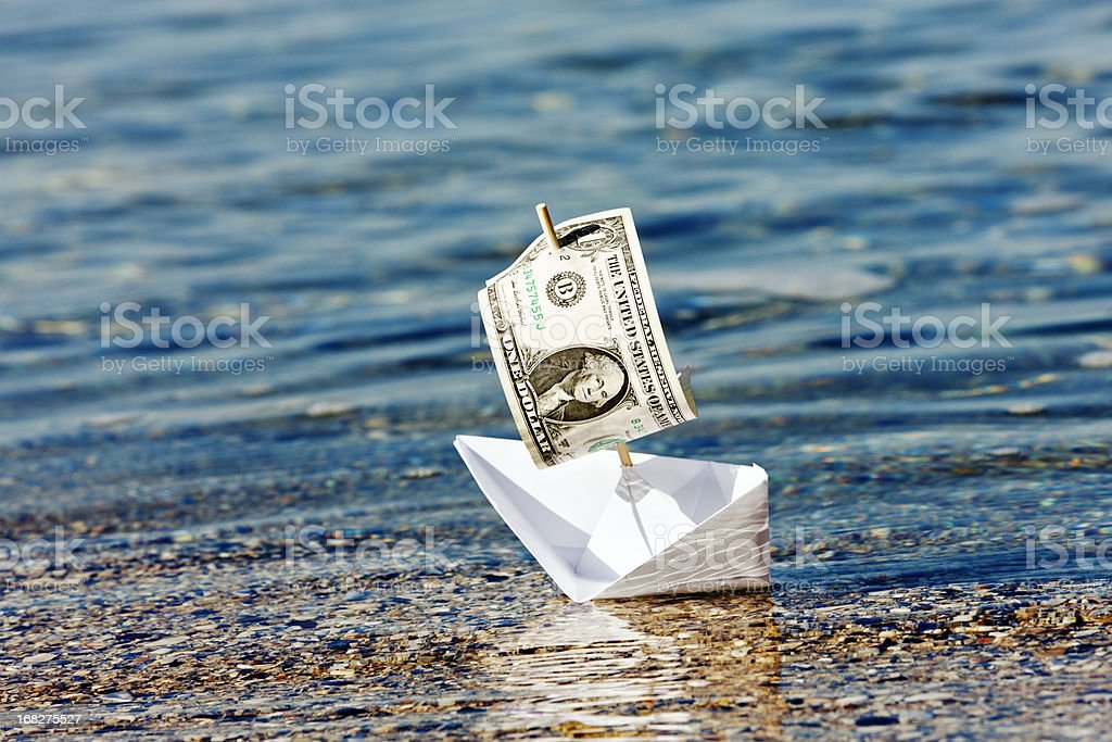 Paper boat with $1 sail stuck in shallows: money problems? stock photo