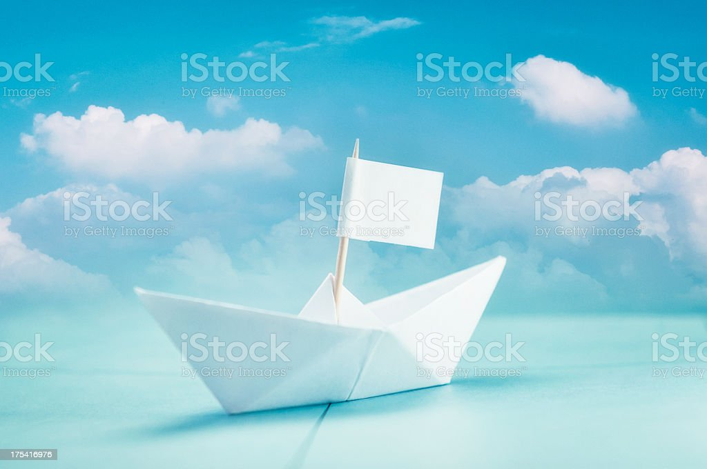 Paper boat with cloudy blue sky stock photo