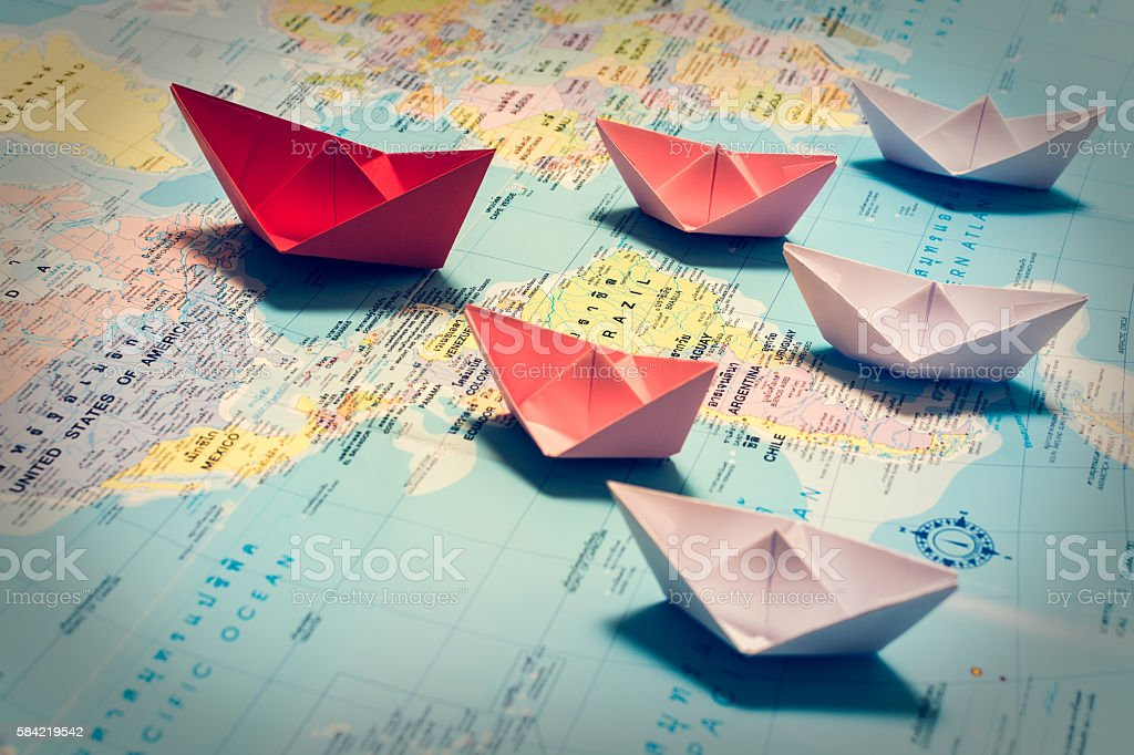 Paper boats following a red leader boat stock photo