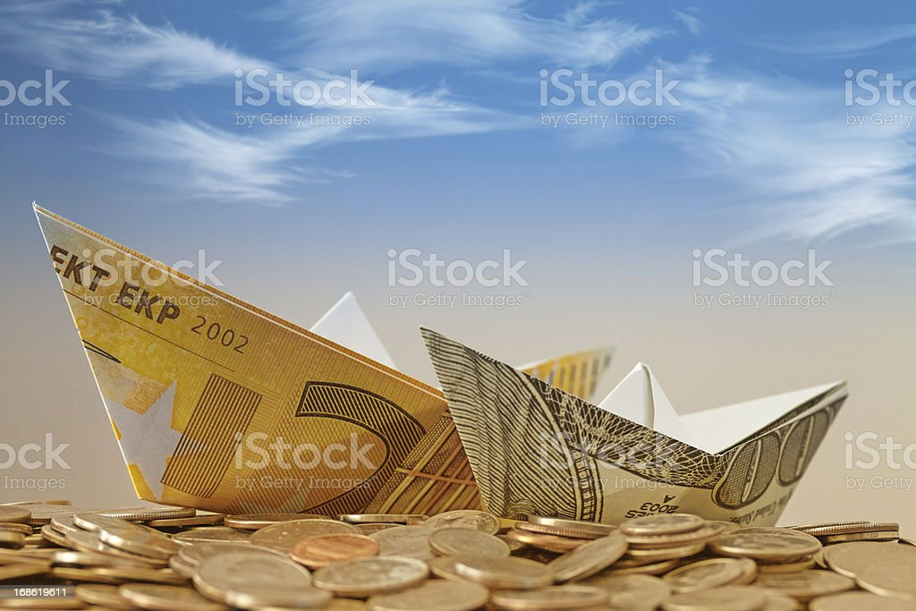 Paper boats on the coin heap royalty-free stock photo