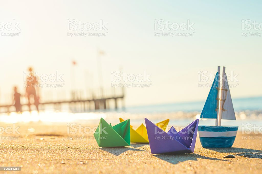 paper boats, wood boat and walking people at the beach stock photo