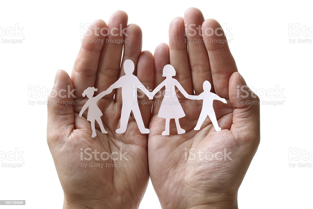 Paper chain family protected in cupped hands stock photo