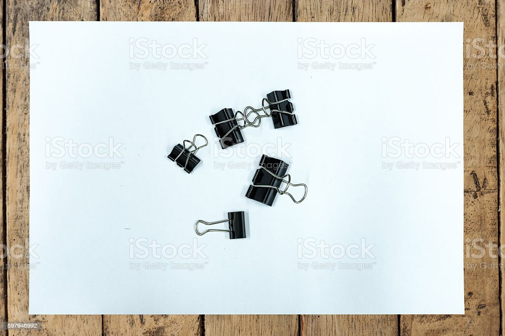 Paper clip and white paper on wood table stock photo
