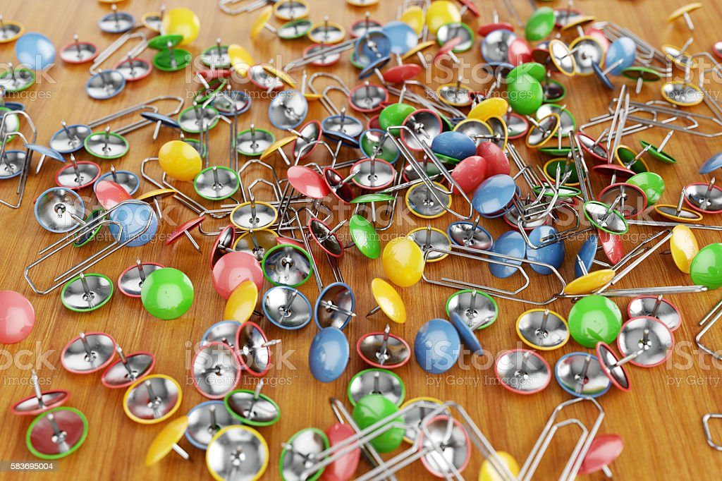 Paper clips and drawing pins scattered on a table. stock photo