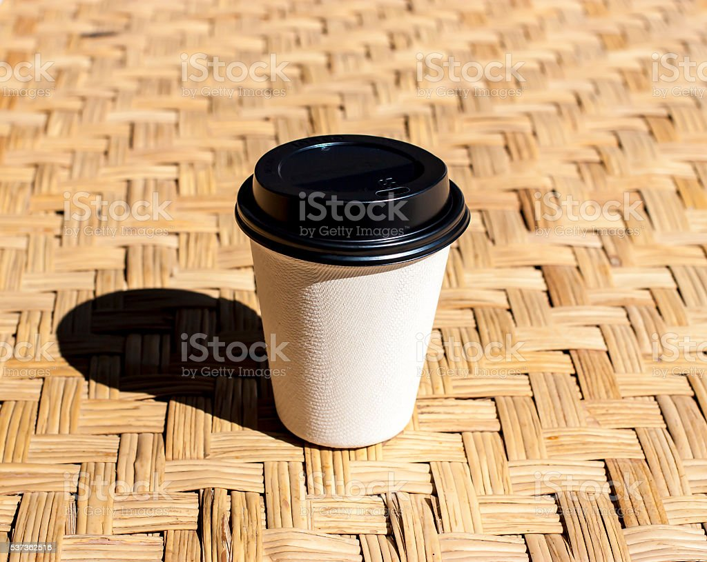 paper coffee cup put on rattan mat stock photo