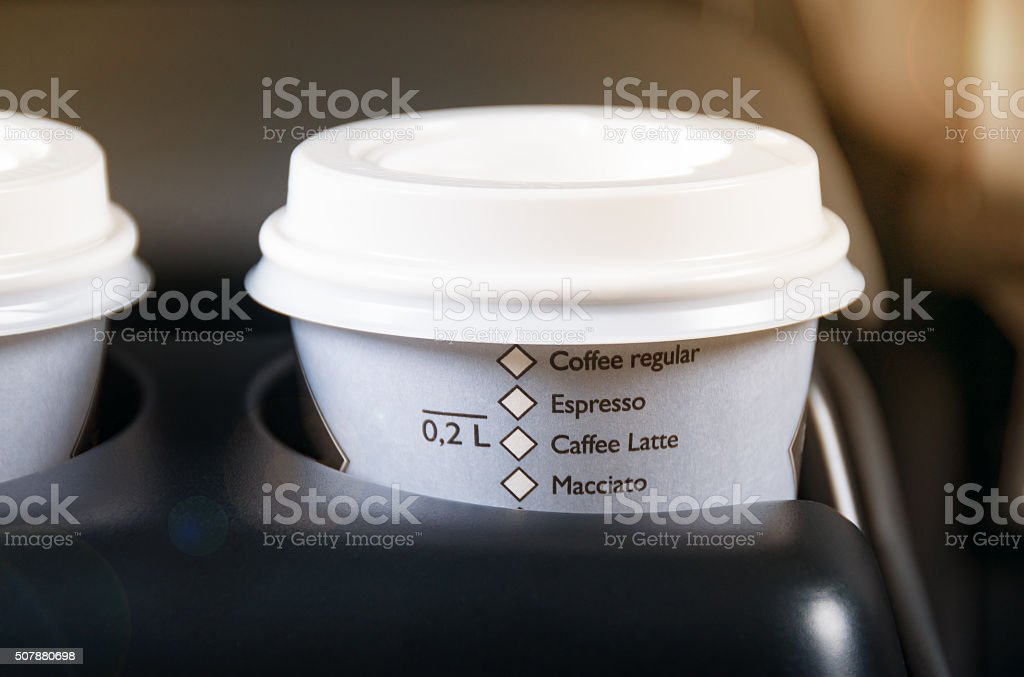 Paper coffee cups inside car cup holder. stock photo