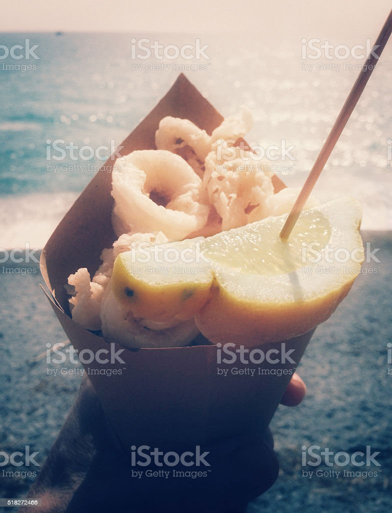 Paper cone full of fried seafood at the seaside stock photo