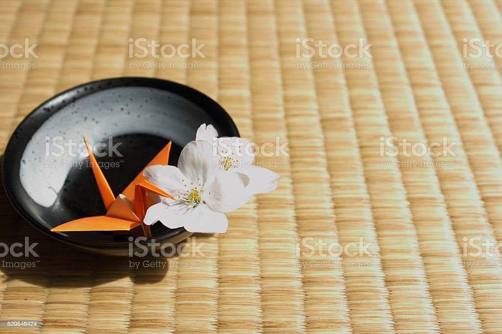 Paper crane and cherry blossoms on traditional Japanese Tatami mat stock photo