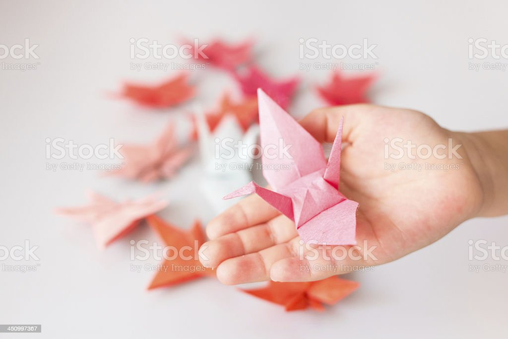 Paper crane on the palm and autumn leaves stock photo