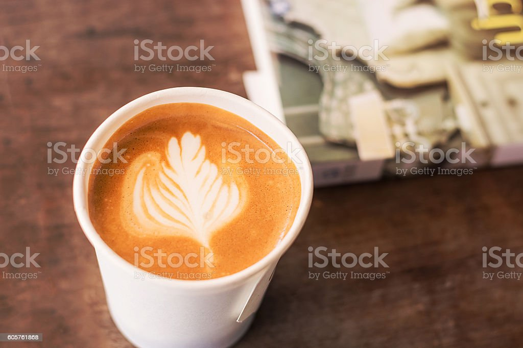 Paper cup of coffee latte on wooden table stock photo