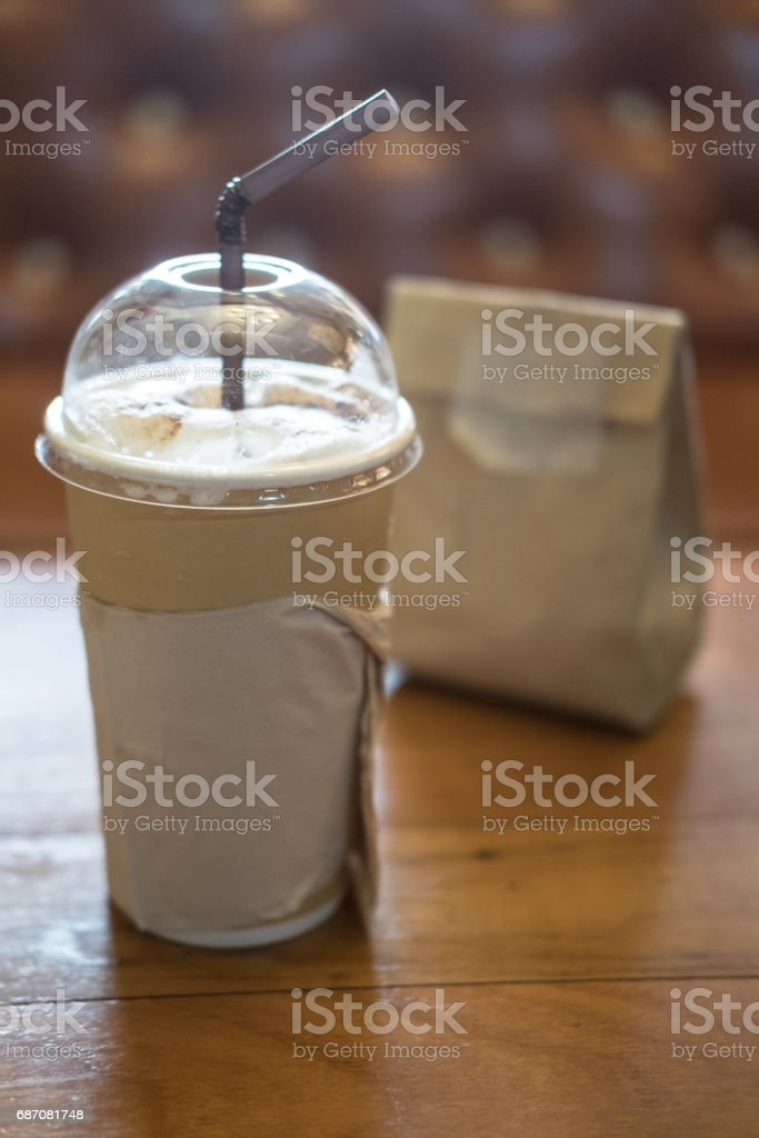 Paper cup of iced coffee on wooden table. Slow life concept stock photo