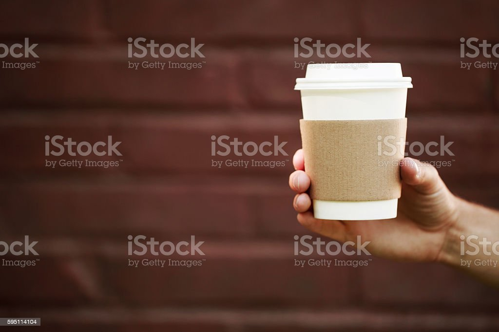 Paper cup of takeaway coffee in the hand stock photo