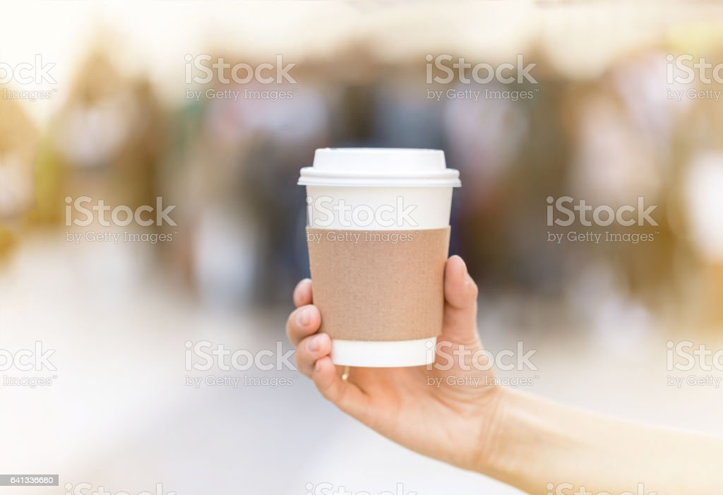 Paper cup of takeaway coffee in the hand. Place for your text or logo. stock photo