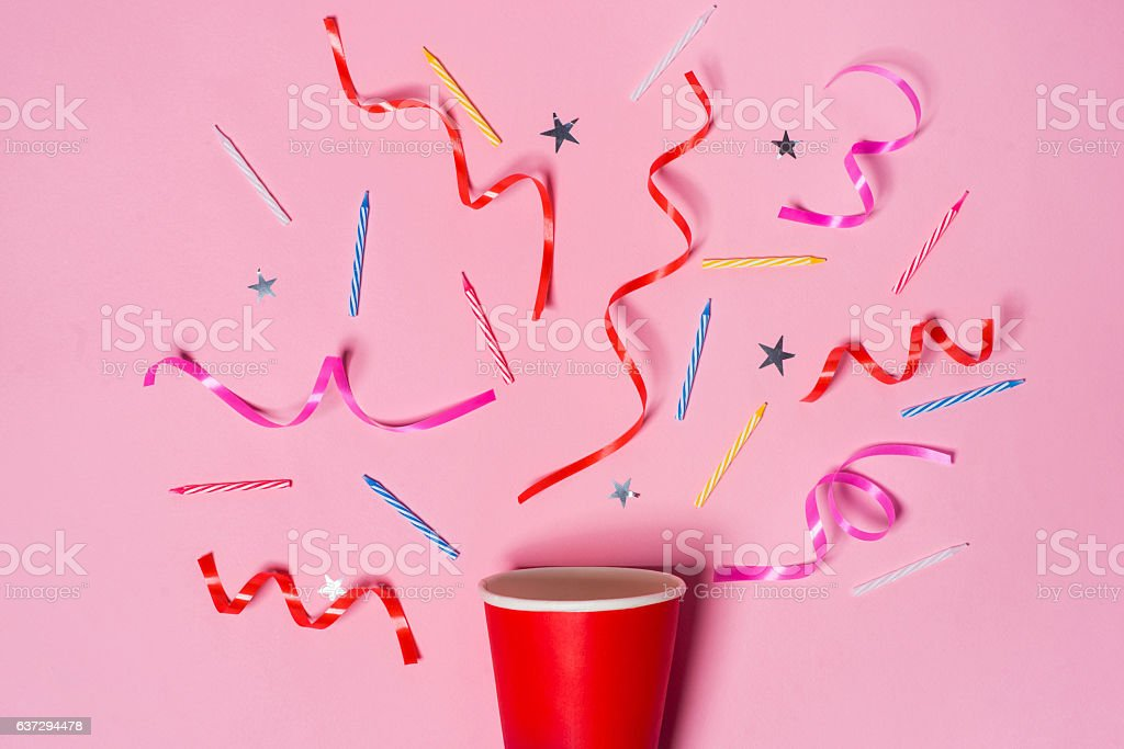 Paper cup with colorful party streamers on pink background. stock photo