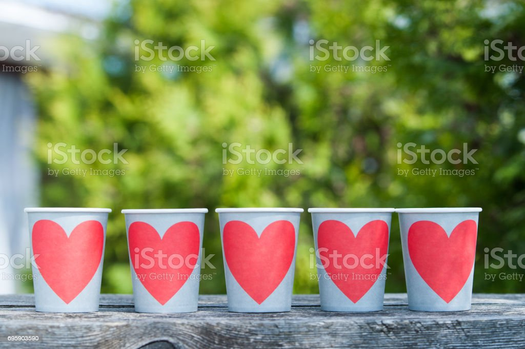 Paper cups with hearts lined up in a row against the background of a green garden. The theme of love, good, peace. I love summer, tea party, time of love, love party stock photo