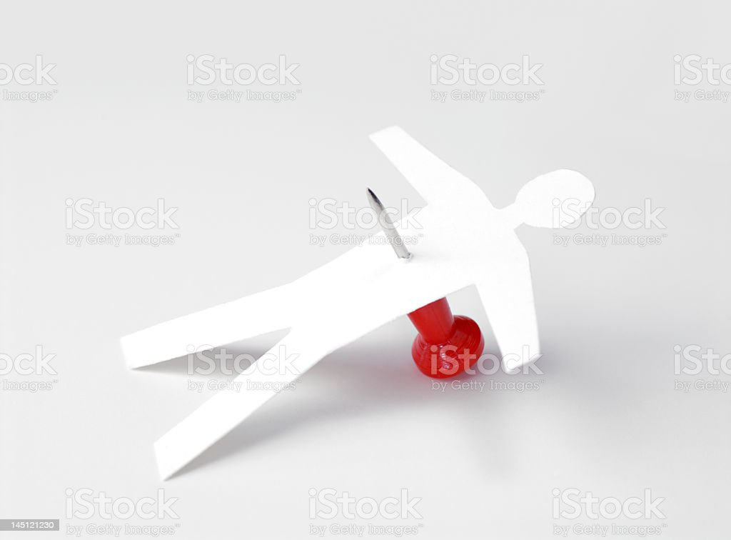 Paper cut out man stabbed with a map pin like a voodoo doll stock photo