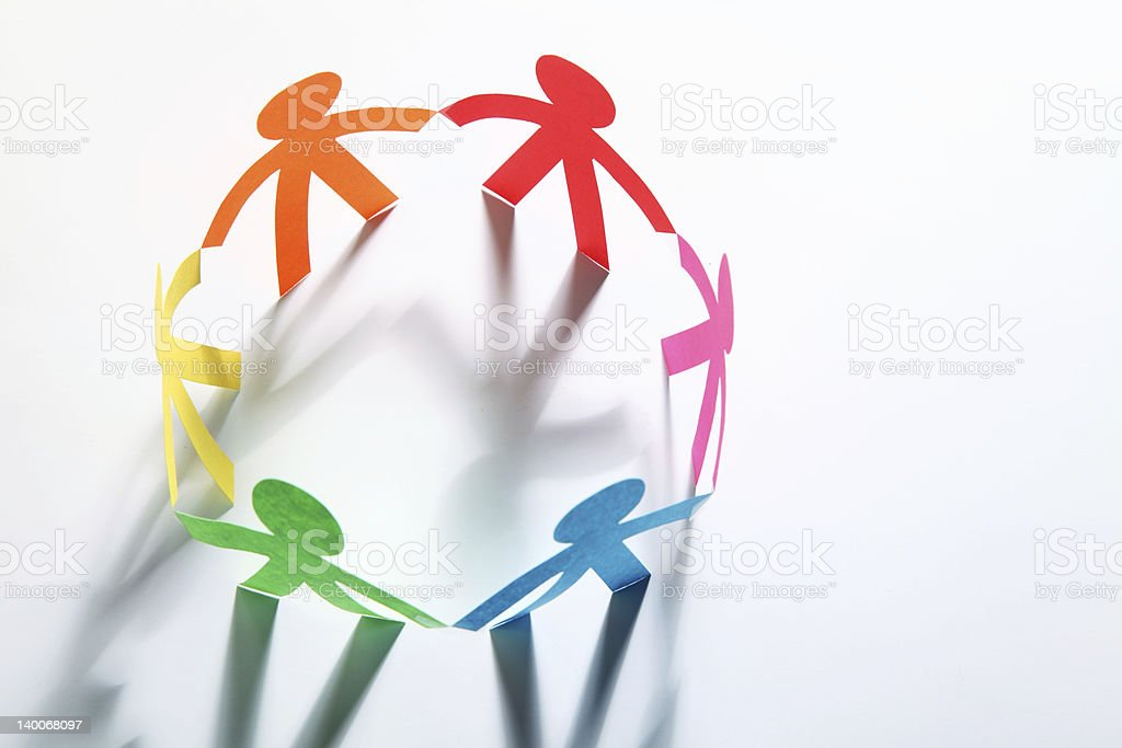 Paper cutouts of colorful people holding hands in a circle stock photo