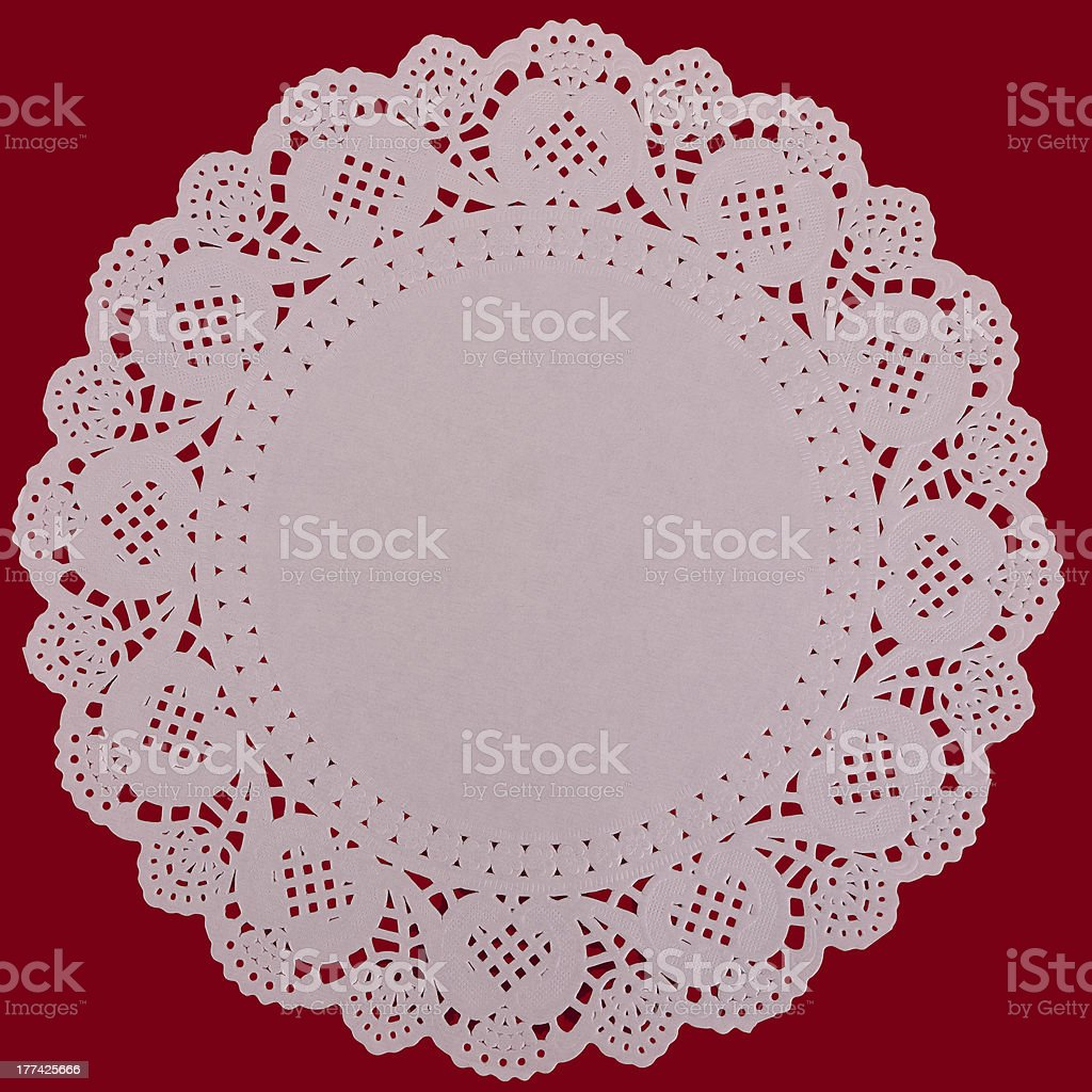 Paper doily lacy background, over red stock photo