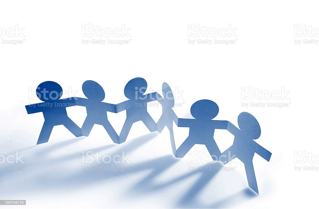 Paper dolls holding hands against white background stock photo