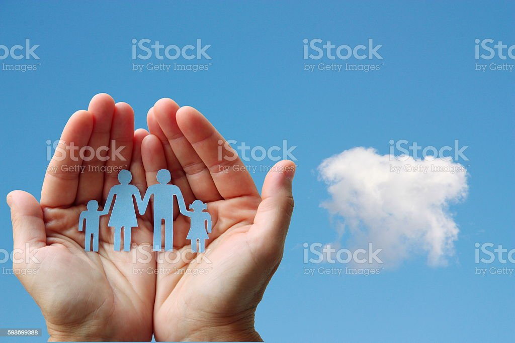 Paper family in hands on blue sky background welfare concept stock photo