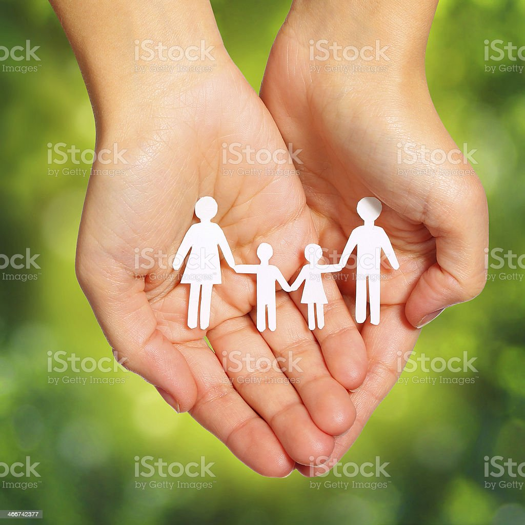 Paper Family in Hands over Green Sunny Background. Family stock photo
