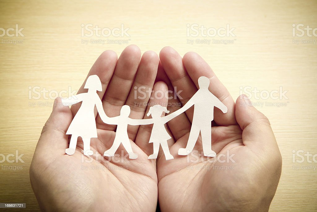 Paper family in hands with wooden texture background stock photo