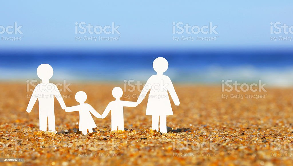 Paper Family on the beach. stock photo