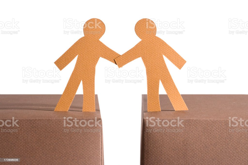 Paper figures with a gap between them holding hands on boxes royalty-free stock photo