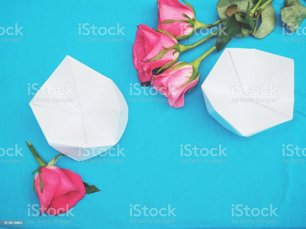Paper fortune teller and pink rose on blue background stock photo