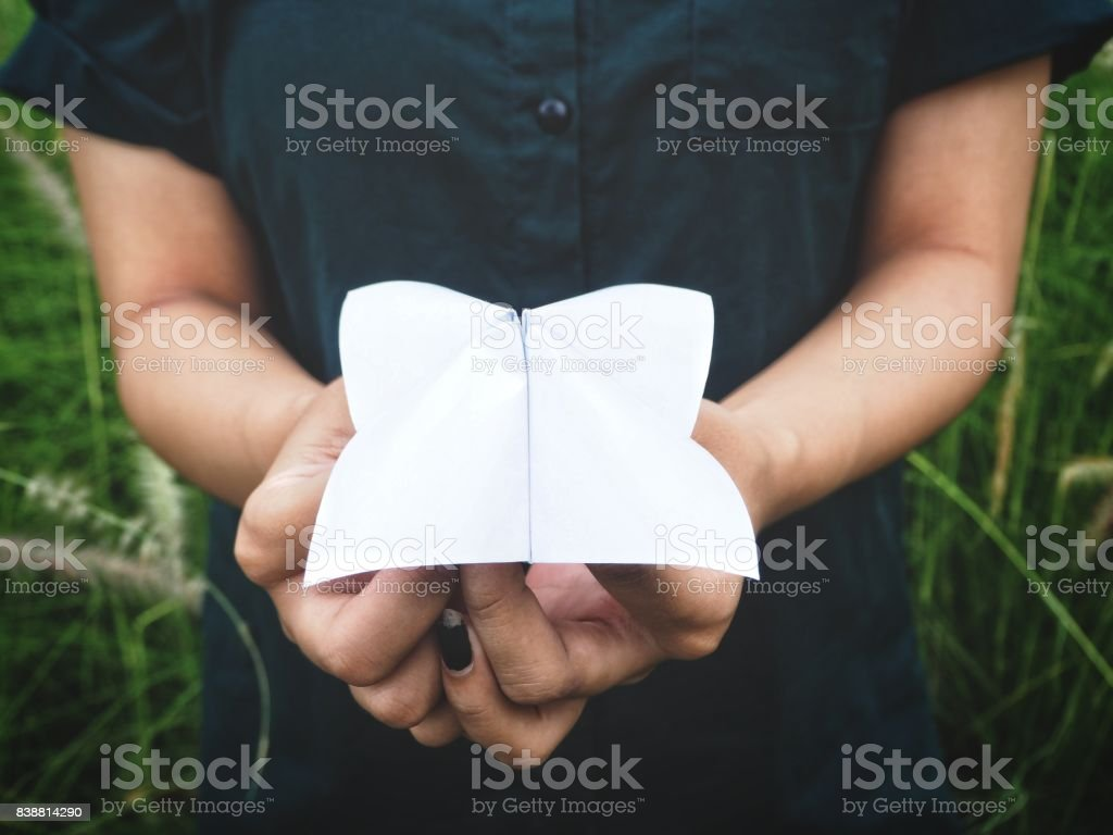 Paper fortune teller on hands with grass flowers stock photo