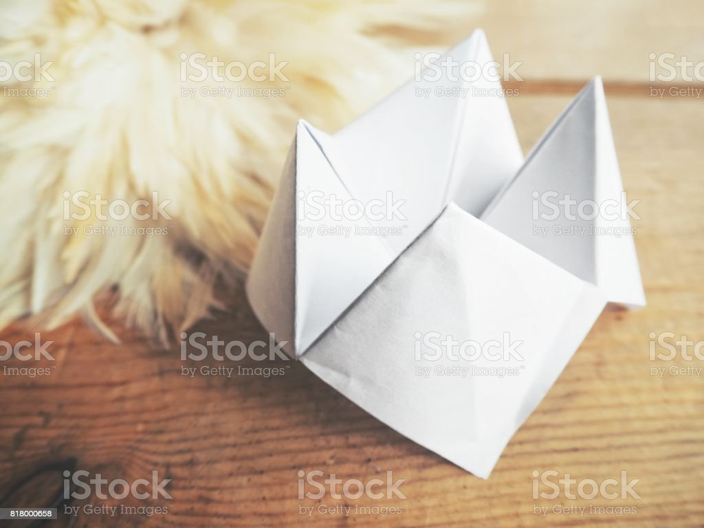 Paper fortune teller with white feathers stock photo