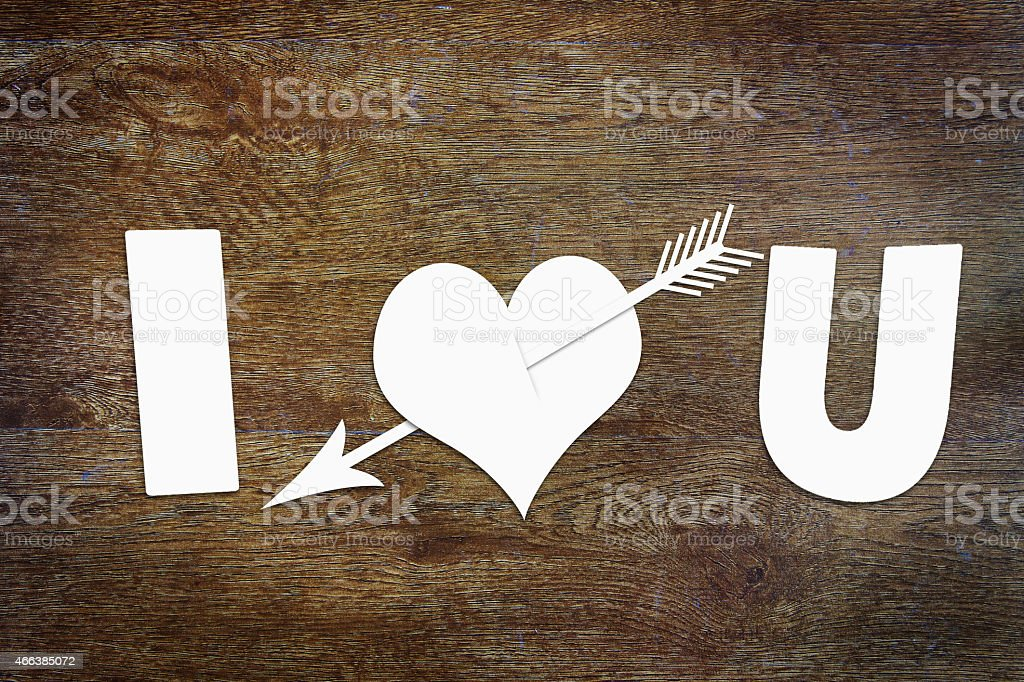 Paper heart pierced by an arrow on wooden background stock photo