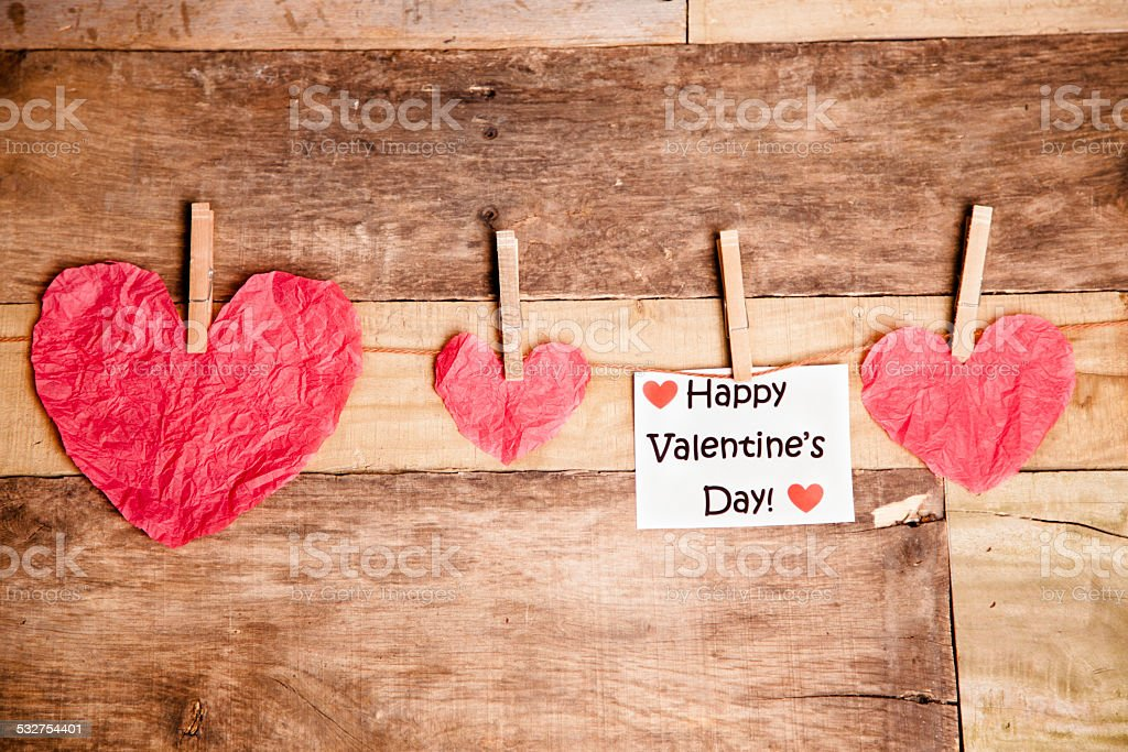 Paper hearts on string. Happy Valentine's Day note. Wooden table. stock photo