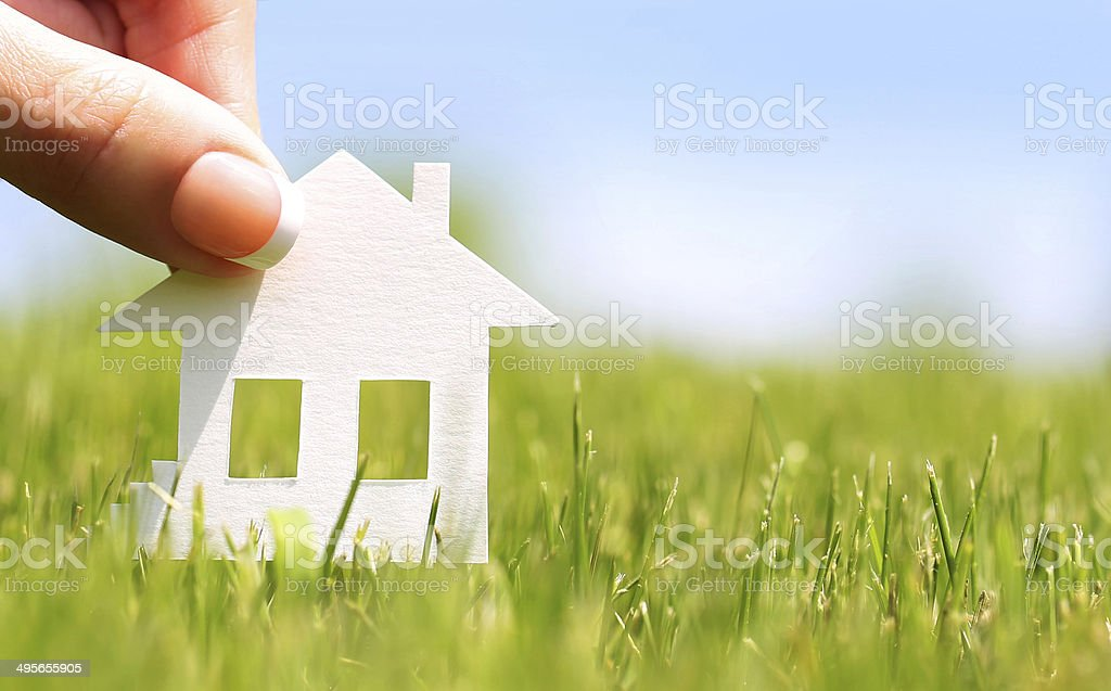 Paper house in green grass over blue sky. Concept stock photo