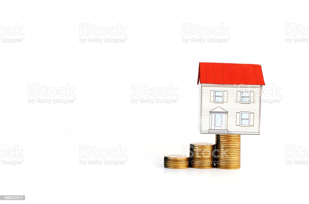 paper house on coins stack on white background stock photo