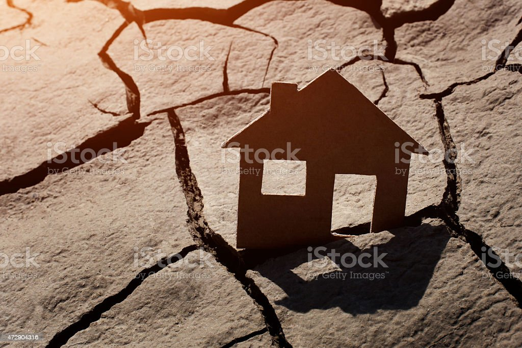 Paper house on cracked earth stock photo