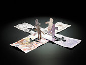 paper men of various currencies facing each other