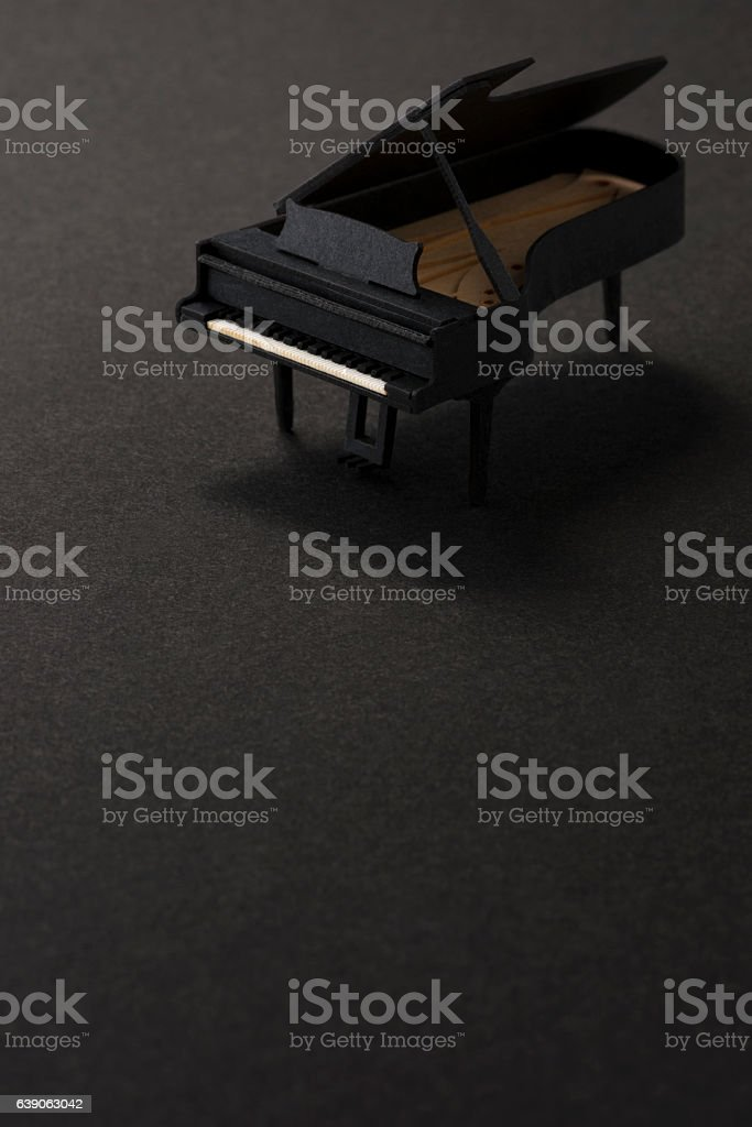 paper miniature piano on black background stock photo