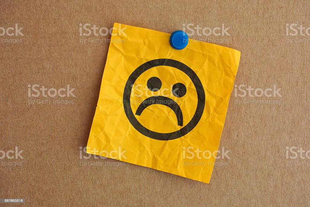 Paper note with sad face stock photo