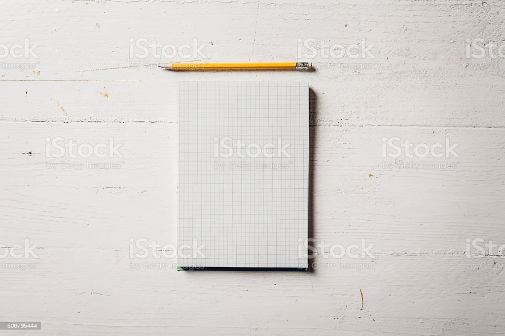 Paper notebook with pencil on a white wood table stock photo