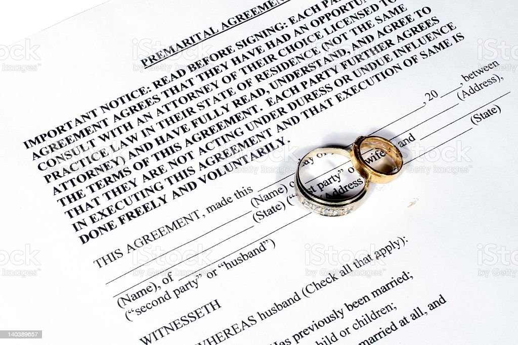 Paper of prenuptial agreement with two rings on top stock photo