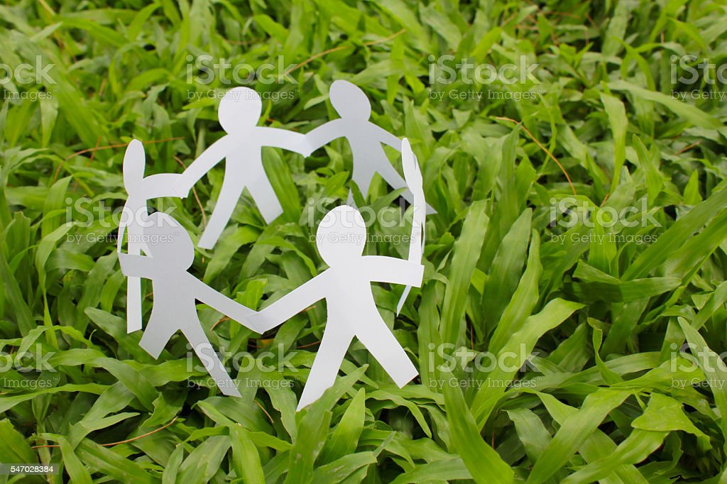 Paper people in a circle with green grass background Lizenzfreies stock-foto