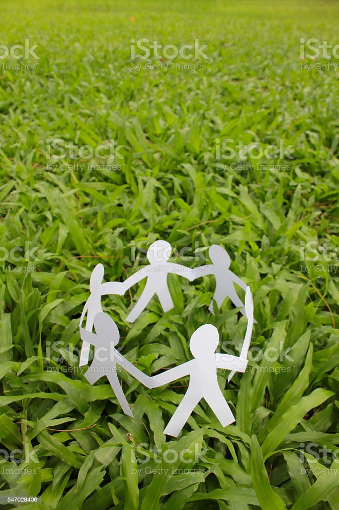 Paper people in a circle with green grass background. Lizenzfreies stock-foto