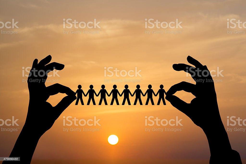 Paper people in man hand over sunset of silhouette stock photo