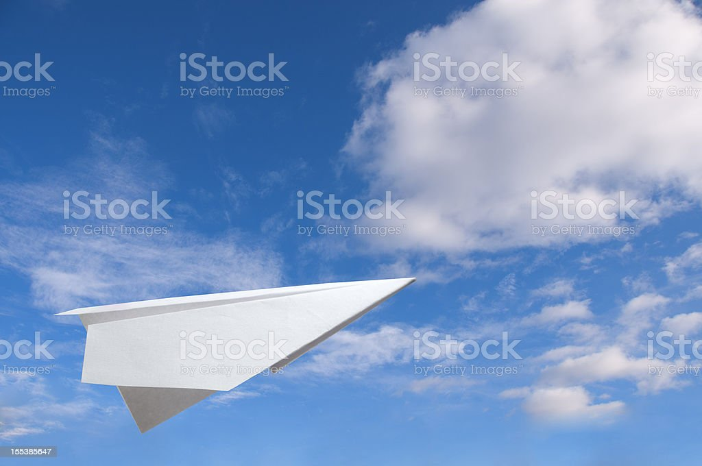 Paper plane flying in the air against a blue sky royalty-free stock photo